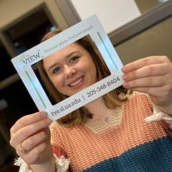 First Year Experience student poses with a New View photo frame magnet.